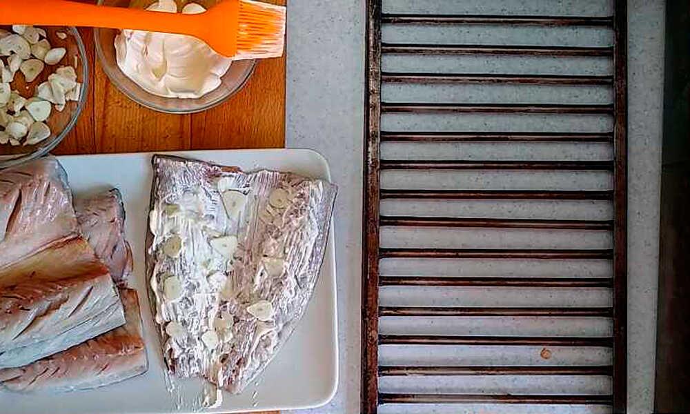 Обмазывание тушек рыбы майонезом и добавление чеснока