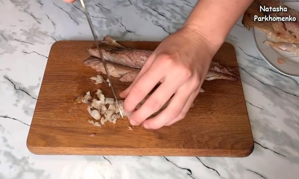 Нарезают скумбрию на мелкие кусочки