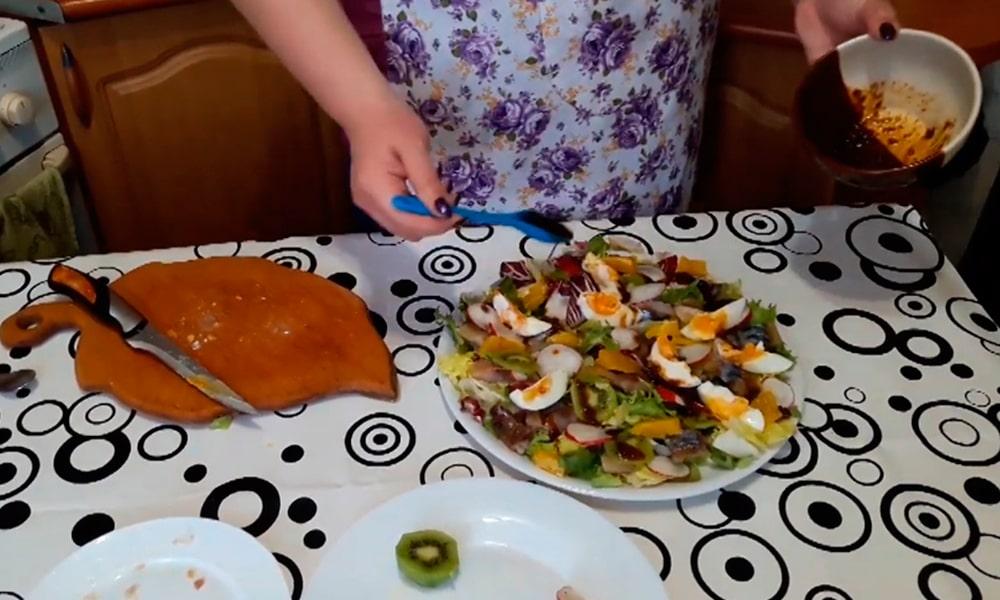Поливают салат соусом
